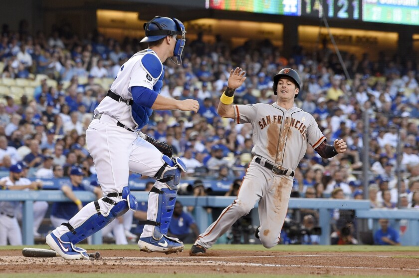 San Francisco Giants' Evan Longoria, right, scores after Kevin Pillar grounded out as Dodgers catcher Will Smith stands at the plate during the first inning on Saturday at Dodger Stadium.