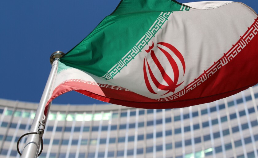 The Iranian flag flies in front of a U.N. building where closed-door nuclear talks take place at the International Center in Vienna.