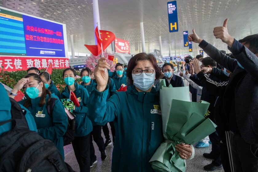 Medical staff members (in green) from Peking Union Medical College Hospital wave national flags before leaving Tianhe airport in Wuhan, China.