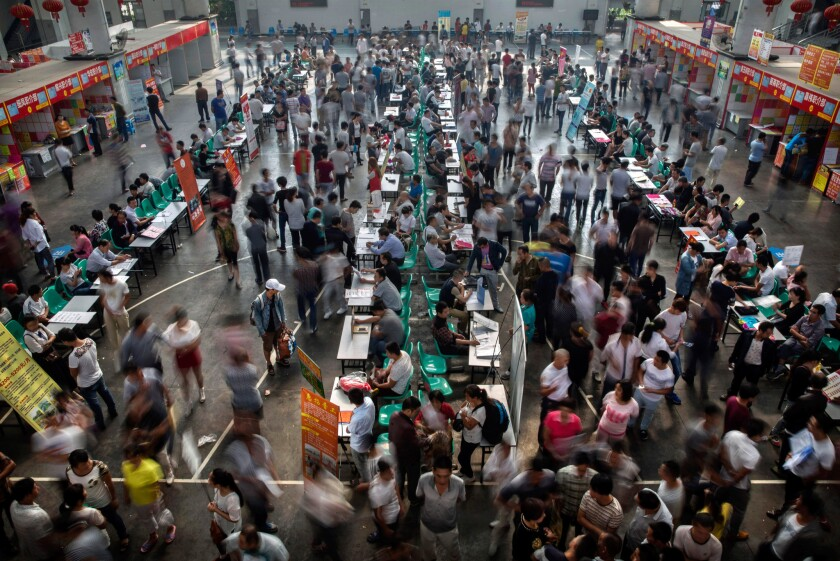 Chinese workers gather around potential employers at a job center in Yiwu, China, on Sept. 18. A slowdown in manufacturing and exports in China is causing global concern that the world's second-largest economy is running out of steam.