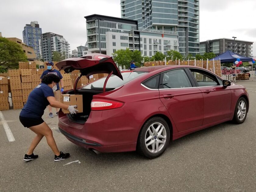 USO volunteer Brigette Jimenez places a box of produce in the back of a vehicle on Saturday. The USO had a drive-through food distribution event for current members of the military and their families near Petco Park as part of Armed Forces Day.