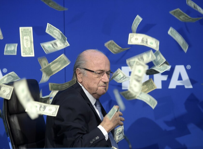 FILE - In this file photo dated July 20, 2015, fake banknotes are symbolically thrown by British comedian Simon Brodkin, at former FIFA president Sepp Blatter during a media conference following the extraordinary FIFA Executive Committee at the headquarters in Zurich, Switzerland. The office of Mic