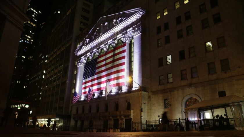 FILE- In this Feb. 17, 2017, file photo, an American flag hangs on the front of the New York Stock E