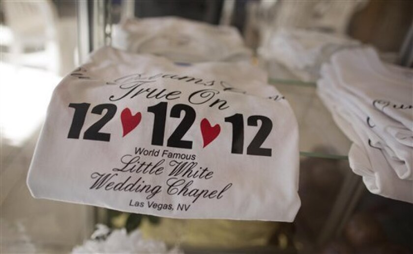 """Tee shirts advertising the 12-12-12 date sit on display at A Little White Wedding Chapel, Tuesday, Dec. 11, 2012, in Las Vegas. These """"once-in-a-century"""" wedding dates have become more important each year as people increasingly look outside Vegas for nontraditional weddings. Once known as the wedding capital of the world, Vegas' share of the U.S. wedding market has fallen by a third since 2004. (AP Photo/Julie Jacobson)"""