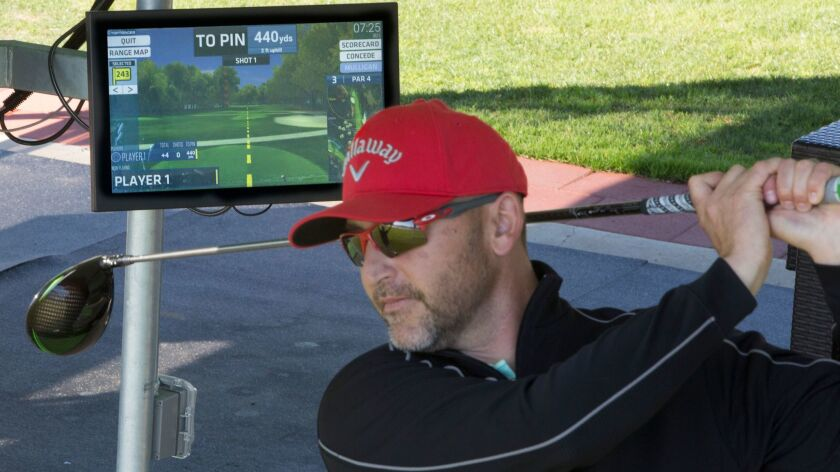 Matt Clay, of Del Mar Golf Center, takes a simulated shot in order to show the features on the compu