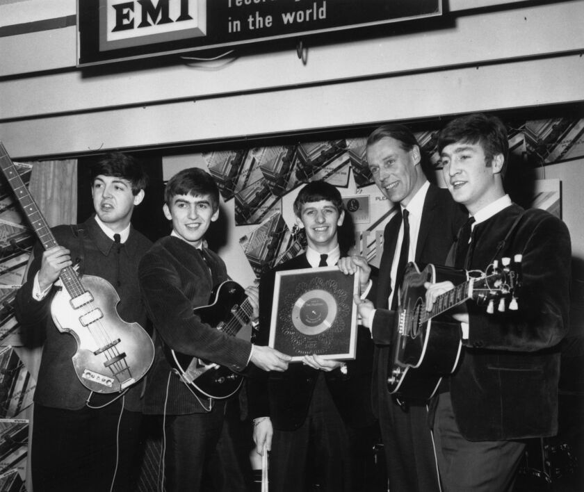 Beatles producer George Martin, second from right, stands with the group as they hold a silver disc marking their record sales in April 1963.