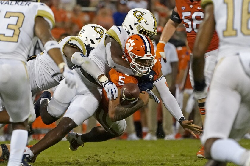 Clemson quarterback D.J. Uiagalelei (5) fumbles as he is hit by Georgia Tech defenders in the second half of an NCAA college football game, Saturday, Sept. 18, 2021, in Clemson, S.C. (AP Photo/John Bazemore)