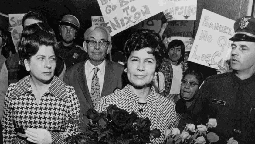 Then U.S. Treasurer Romama Acosta Bañuelos, right, is flanked by security guards and friends who escort her away from demonstrators protesting what they claim was the Nixon administration's attempt to destroy the farm worker's union movement in 1972.