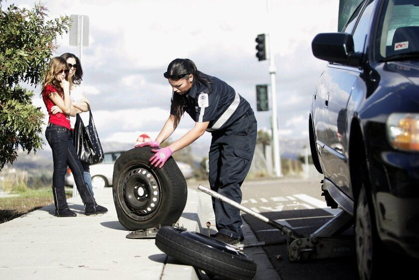 Natalia Mendivil changed a tire for a customer and her daughter last month in San Marcos. Mendivil is one of three women who do roadside assistance for NK Towing & Road Service in Escondido. The women are trained to change a battery, unlock a door, change a tire and make minor, fast repairs to get a motorist back on the road.