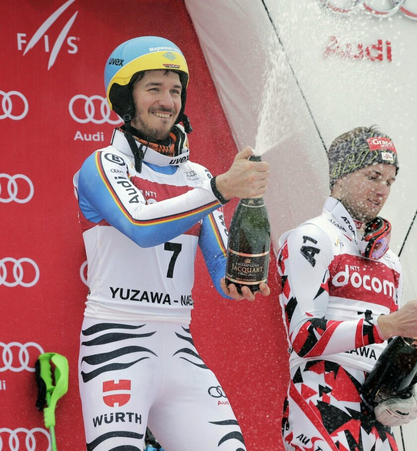Men's World Cup slalom winner Felix Neureuther, left, of Germany opens a bottle of Champagne with third placer Marco Schwarz of Austria during the awarding ceremony at the FIS Alpine Ski World Cup Sunday, Feb. 14, 2016, in Yuzawa, northern Japan. Neureuther, fifth after the first run, clocked a tim