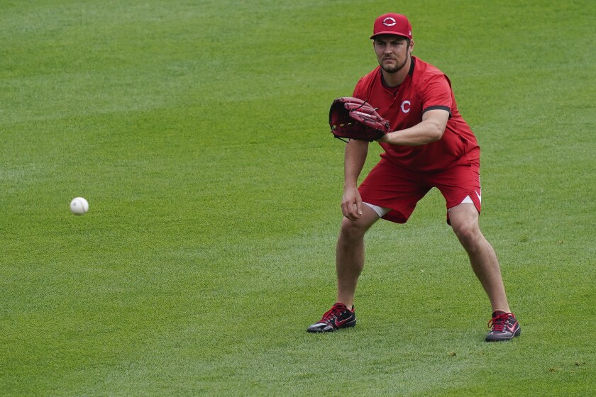 Cincinnati Reds pitcher Trevor Bauer warms up in the outfield during team baseball practice at Great American Ball Park in Cincinnati, Wednesday, July 8, 2020. (AP Photo/Bryan Woolston)