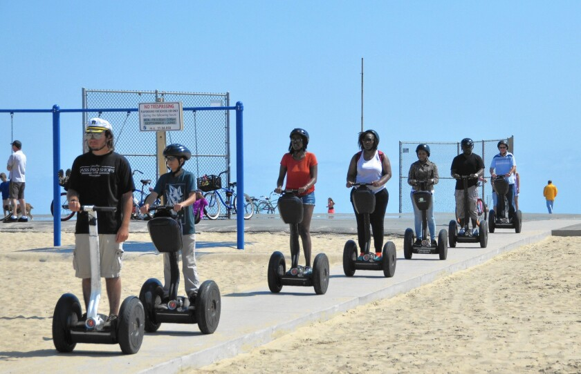 A group of scooter riders approaches the Balboa Peninsula boardwalk in 2016.