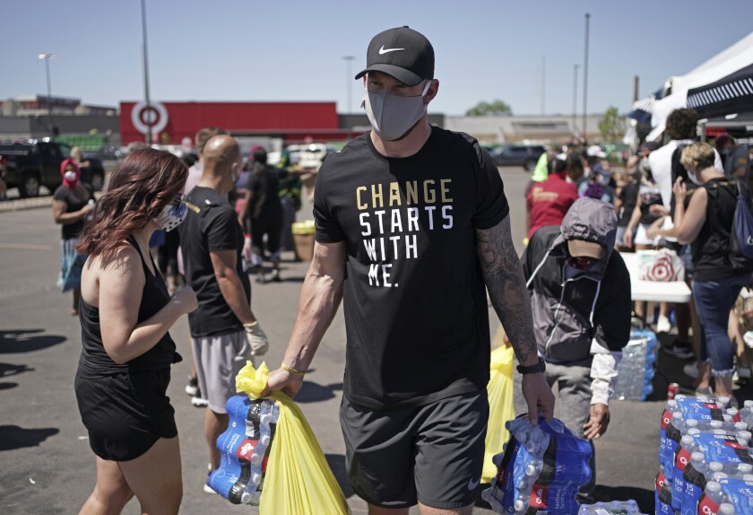 """In this photo taken Friday, June 5, 2020, Minnesota Vikings NFL football player Kyle Rudolph helps a woman carry items to her car at the """"Change Starts with Me"""" food and household supply giveaway outside a Cub Foods store in Minneapolis. George Floyd was killed less than three miles from the stadium where the Minnesota Vikings play, so this global unrest over racial relations and justice hit awfully close to home for the team. (Brian Peterson/Star Tribune via AP)"""