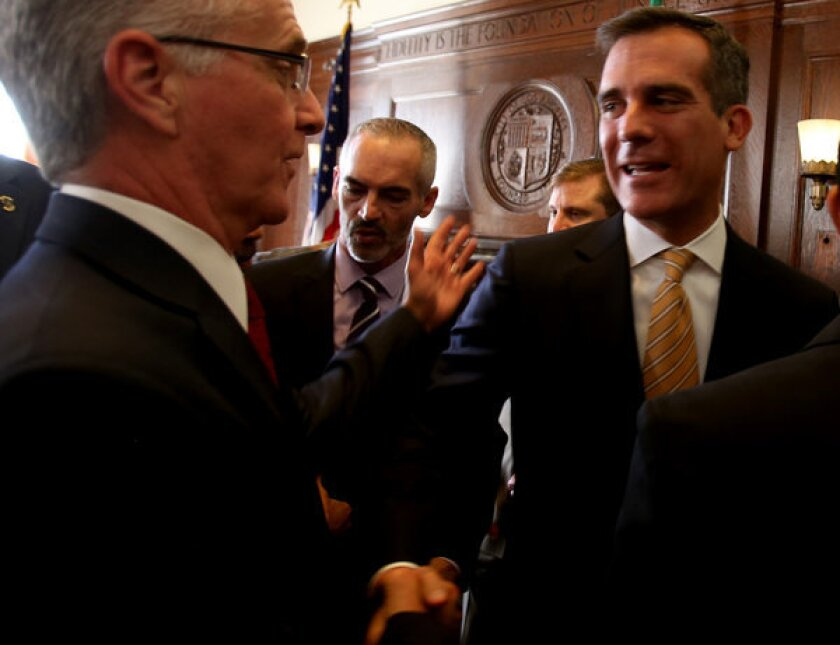 Los Angeles Mayor Eric Garcetti, right, shakes hands with Councilman Paul Krekorian after announcing that an agreement has been reached in contract negotiations with workers at the Department of Water and Power during a press conference at City Hall.