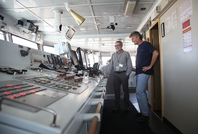 New seafloor maps have been released by Scripps researcher David Sandwell, left, He and colleagues like Melville Captain Chris Curl,  at right, both on the bridge of the Melville, used computer techniques to map out vast areas of the ocean floor that hadn't been surveyed yet.