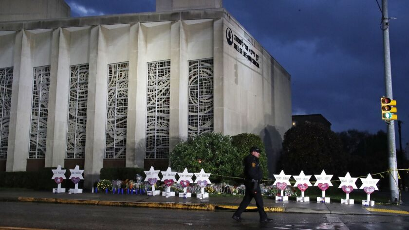 A police officer walks past the Tree of Life Synagogue in Pittsburgh, Penn. on Oct. 28. Critics say Gab, a social media site apparently used by the synagogue shooting suspect, has become a breeding ground for white nationalists, neo-Nazis and other extremists.