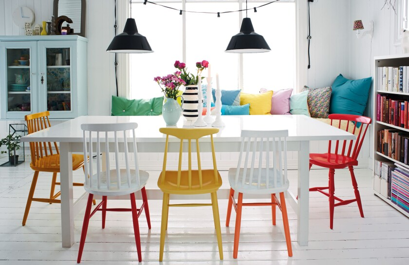 """In Will Taylor's new book, """"Bright Bazaar: Embracing Color for Make-You-Smile Style,"""" colorful chairs placed around a white table make the dining room a focal point."""