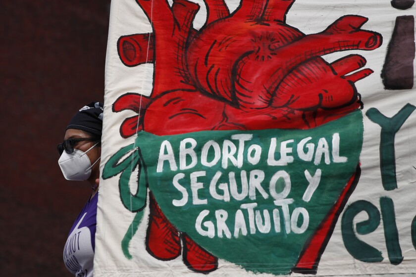 """A woman holds a banner reading in part, in Spanish, """"Abortion Safe and Legal"""" during a demonstration"""