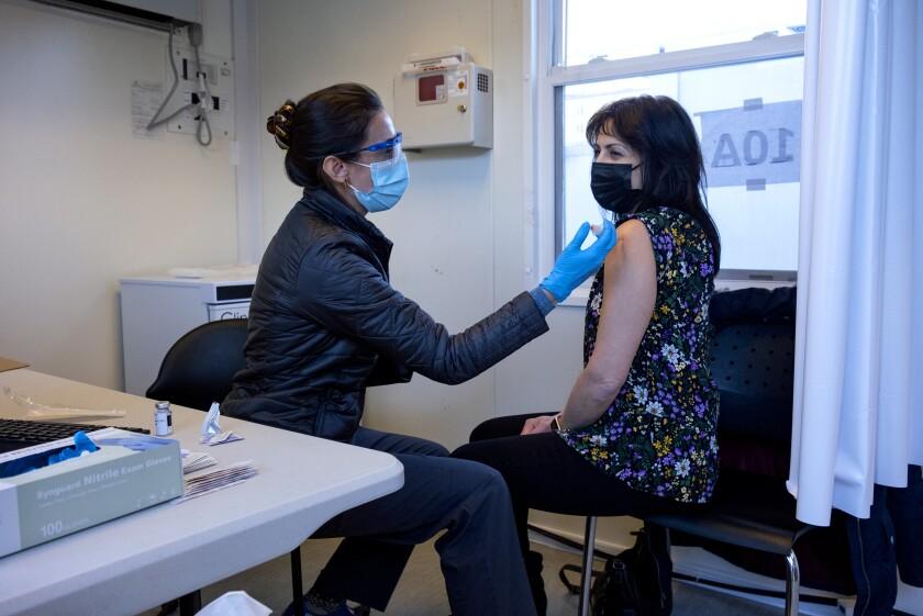 La enfermera Sarah Gonzalez le aplica a Claudia Zain su primera dosis de la vacuna contra el COVID-19