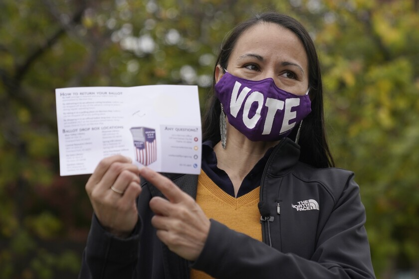 FILE - In this Oct. 20, 2020, file photo, Rep. Sharice Davids, D-Kan., talks to the media after depositing her advance ballot in Mission, Kan. Rep. Davids tested positive Friday, Aug. 6, 2021, for COVID-19 despite being vaccinated against it and is in isolation. Davids said in a statement that she has had only mild symptoms and that she got tested after undergoing outpatient surgery involving the parathyroid glands in the neck that regulate calcium levels in the blood.(AP Photo/Charlie Riedel, File)