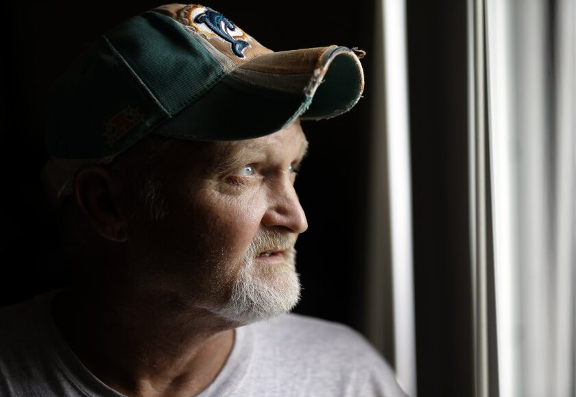 In this Oct. 28, 2015 photo, John Davis poses for photos at his home in Port Charlotte, Fla. Davis, a 49-year-old construction worker unemployed because of health problems, is among those who cannot get health insurance through HealthCare.gov because the law prevents people below the poverty line f