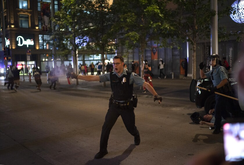 """FILE - In this Aug. 26, 2020, file photo, police spray a substance to clear the area where a colleague was down on the Nicollet Mall in Minneapolis. Two men from Minnesota and North Carolina who prosecutors say are members of an anti-government extremist group have been charged with terrorism counts for allegedly building weapons they believed were going to Hamas. They are allegedly members of the """"Boogaloo Bois."""" The investigation into the men began after they posted messages on social media about inciting violence after the May 25 death of George Floyd. (Jeff Wheeler/Star Tribune via AP, File)"""