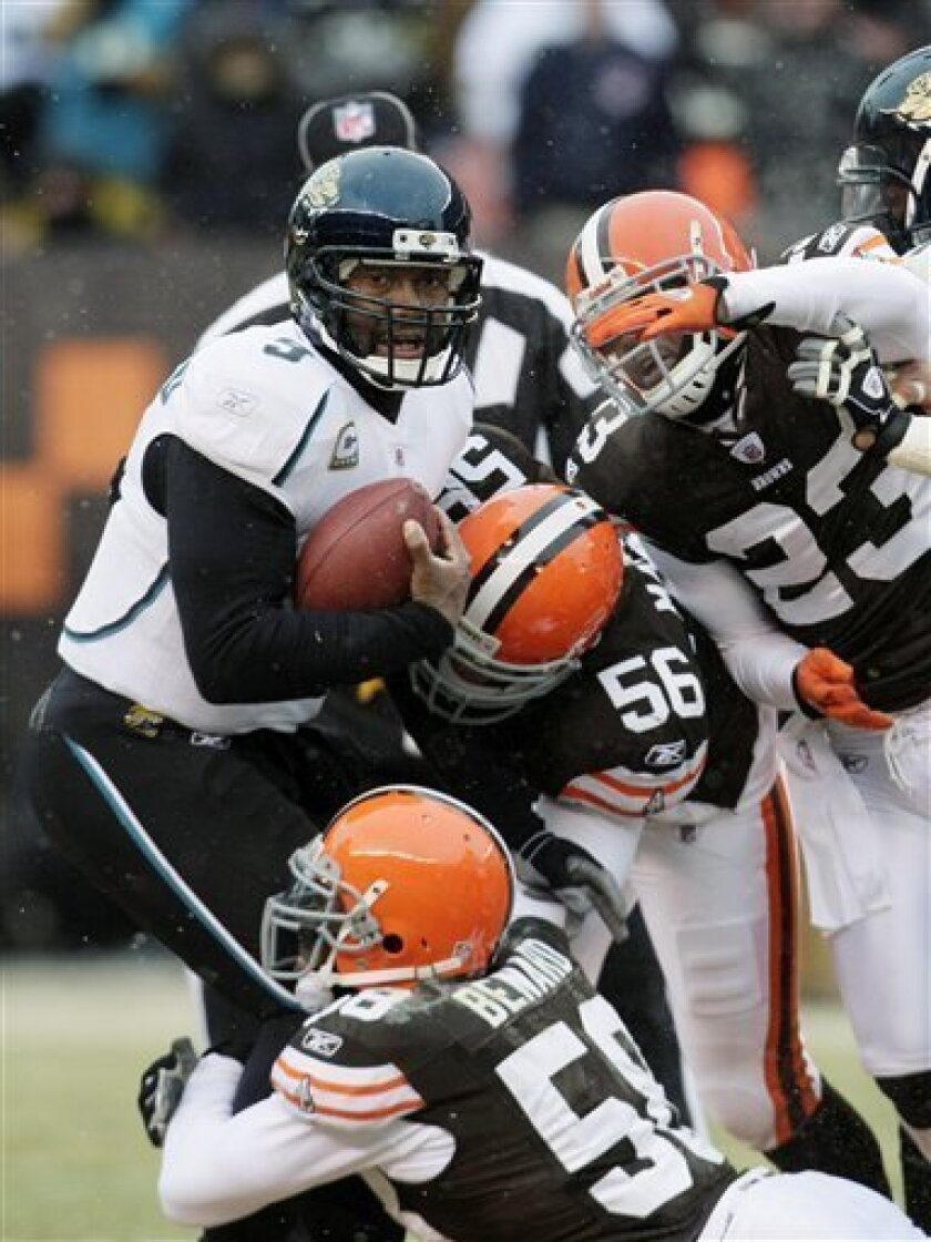 Jacksonville Jaguars quarterback David Garrard is tackled by Cleveland Browns defensive end Marcus Benard (58), Kaluka Maiava (56) and Hank Poteat (23) in the second quarter of an NFL football game Sunday, Jan. 3, 2010, in Cleveland. (AP Photo/Tony Dejak)