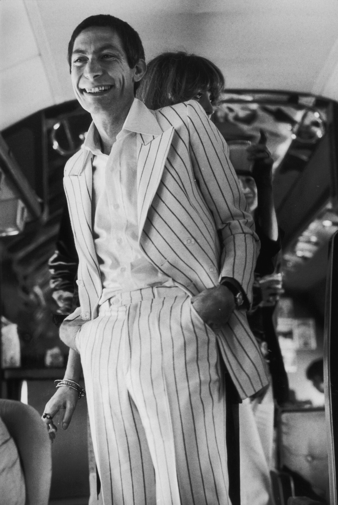 A black-and-white photo of Rolling Stones drummer Charlie Watts in a striped suit.