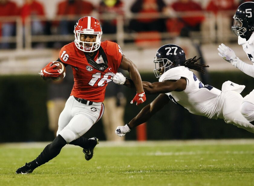 Georgia wide receiver Isaiah McKenzie (16) tries to escape from Georgia Southern linebacker Ironhead Gallon (27) in the first half of an NCAA college football game Saturday, Nov. 21, 2015, in Athens, Ga. (AP Photo/John Bazemore)