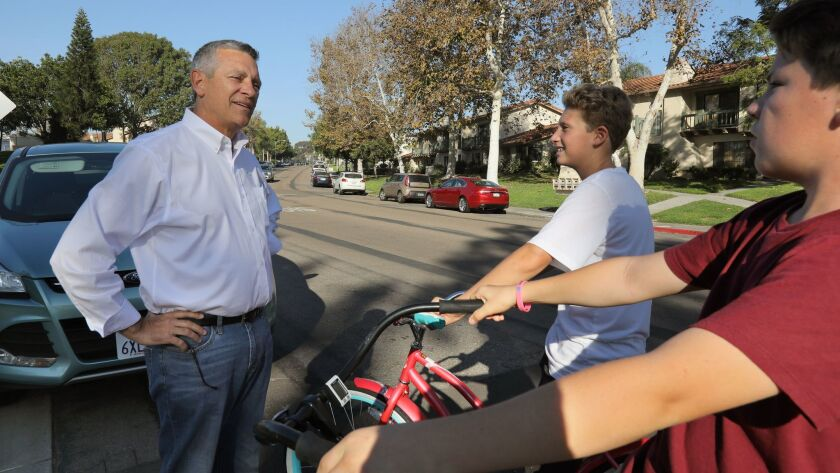 Congressional candidate Doug Applegate speaks to two 14 year olds on their bikes in front of the Carlsbad Fire Station #4 polling place in the 2016 general election.
