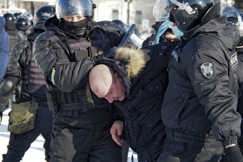 Helmeted police, one holding a baton, stand over a man whom they've bent over.