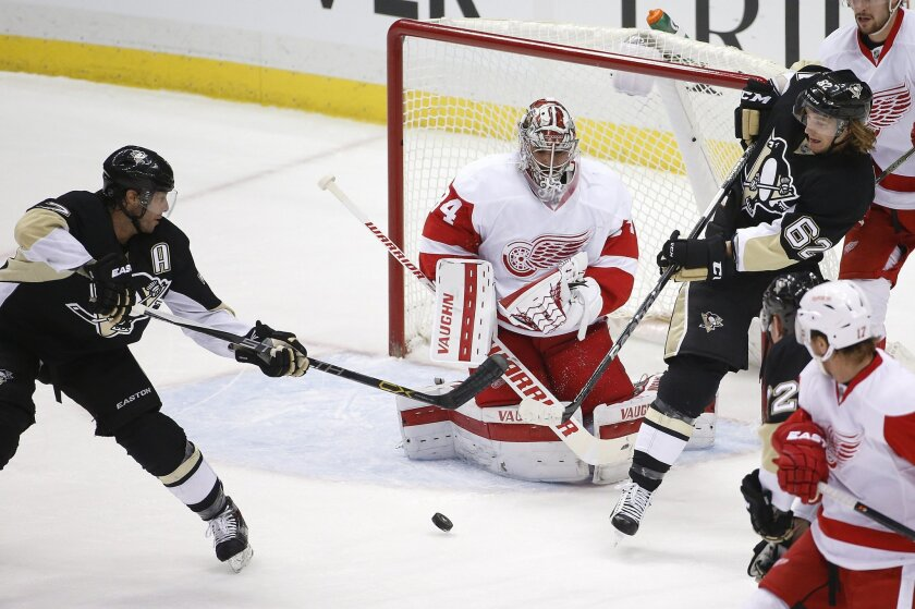 Pittsburgh Penguins' Matt Cullen (7) gets a rebound off Detroit Red Wings goalie Petr Mrazek (34) before putting it between his pads for a goal during the first period of an NHL hockey game in Pittsburgh, Thursday, Feb. 18, 2016. (AP Photo/Gene J. Puskar)