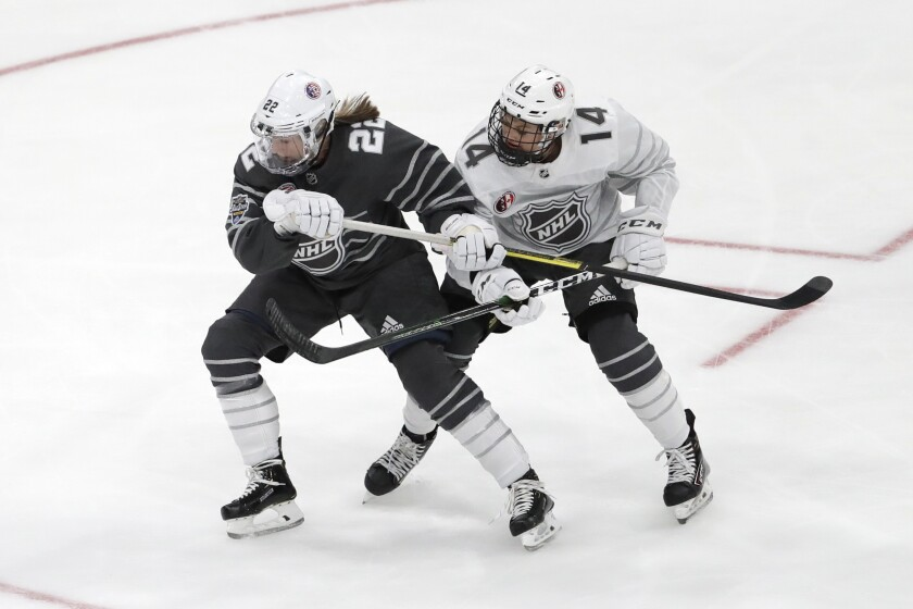 Kacey Bellamy (22) of the United States and Renata Fast (14) of Canada battle for the puck during the first period of the women's three-on-three game during NHL All-Star weekend.