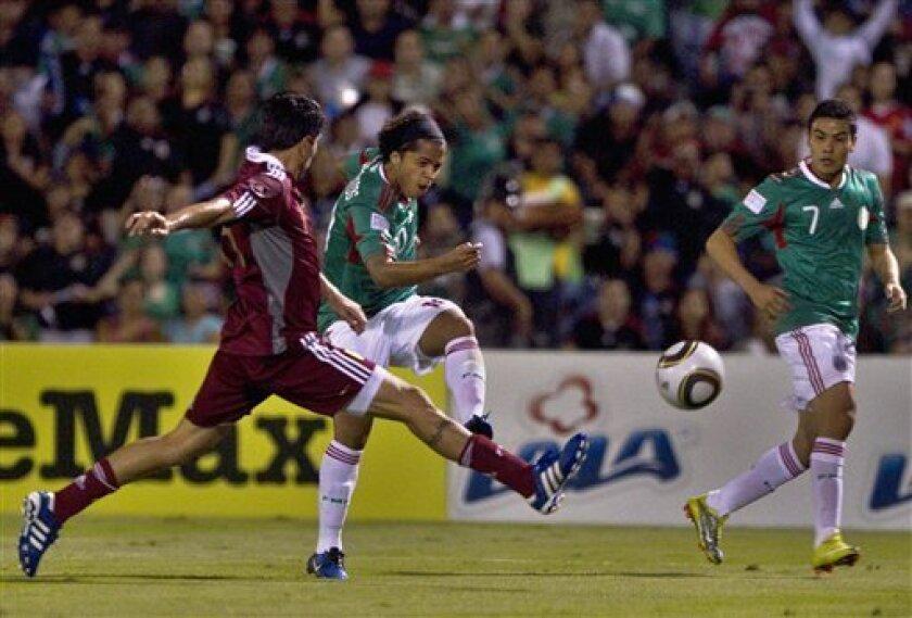 Mexico's Giovani dos Santos, center, kicks to score a goal as Venezuela's Angel Chourio tries to stop him during a friendly soccer match at the Benito Juarez stadium in Ciudad Juarez, Mexico, Tuesday, Oct. 12, 2010. (AP Photo/Guillermo Arias)