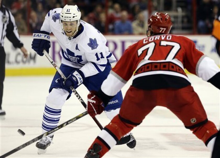 Carolina Hurricanes' Joe Corvo (77) defends as Toronto Maple Leafs' Jay McClement (11) controls the puck during the first period of an NHL hockey game in Raleigh, N.C., Thursday, Feb. 14, 2013. (AP Photo/Gerry Broome)