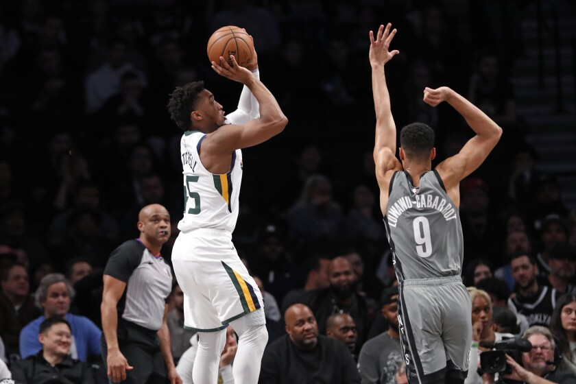 Utah Jazz guard Donovan Mitchell (45) shoots with Brooklyn Nets guard Timothe Luwawu-Cabarrot (9) defending during the second quarter of an NBA basketball game Tuesday, Jan. 14, 2020, in New York. (AP Photo/Kathy Willens)