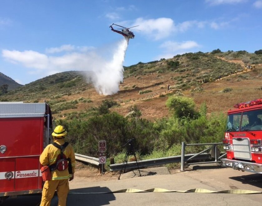 San Diego Fire-Rescue Department crews practiced wildland fire suppression at Mission Trails Regional Park on Wednesday. Firefighters dragged hoses up a steep hill and a helicopter crew drew water from a nearby pond to dump on the brush, as they would during a fire.