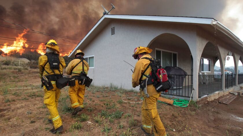 POTRERO, June 20, 2016 | Lakeside firefighters walk next to a home on Highway 94 south of Potrero as