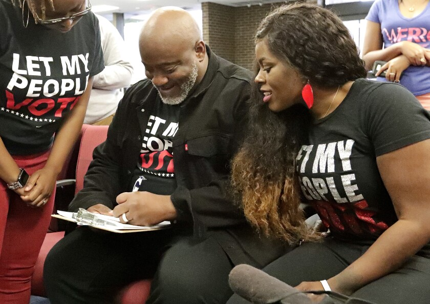 Former felon Desmond Meade fills out a voter registration form as his wife, Sheena, looks on in Orlando, Fla., in 2019.