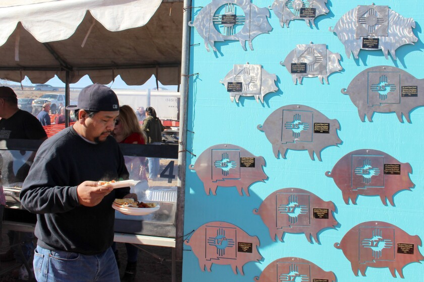 An eater holds plates of carne adovada and enchiladas at the World's Largest Matanza, an all-day fes