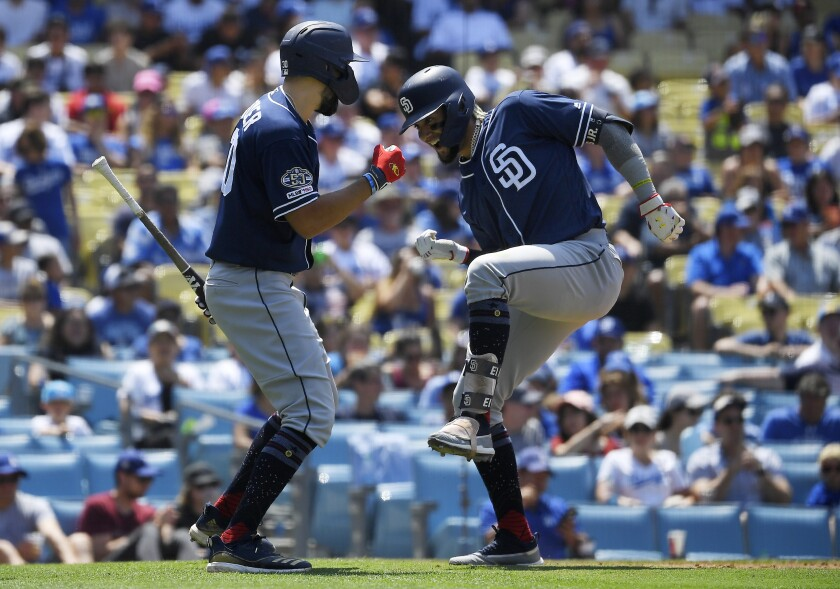 Fernando Tatis Jr., right, celebrates with Eric Hosmer after hitting a three-run home run during the fifth inning of the Padres' game against the Dodgers on Sunday at Dodger Stadium.