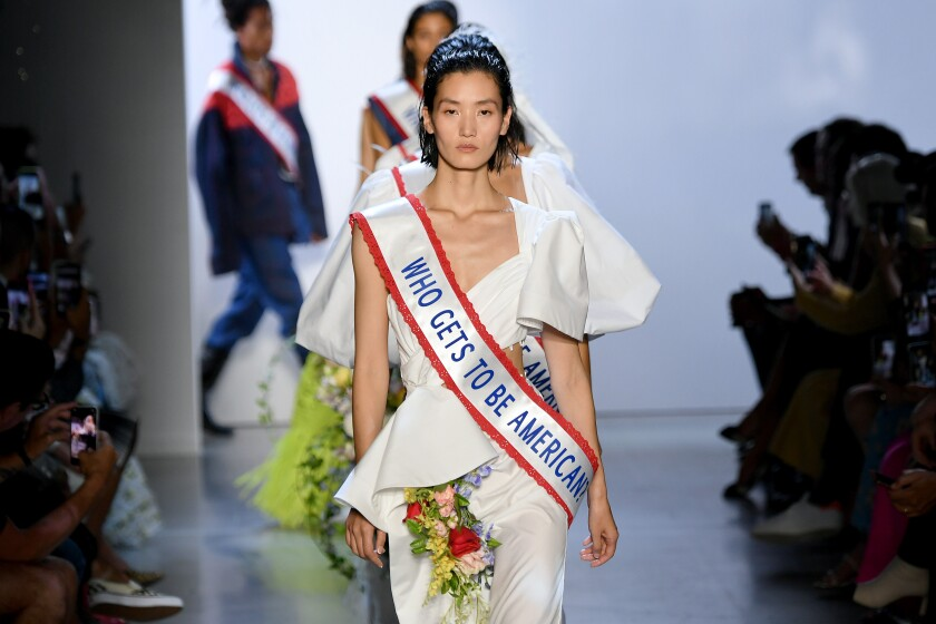 "A runway model in a white dress adorned with flowers and a sash that says ""Who gets to be American?"""