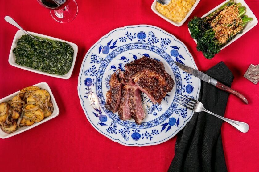 Dear John's ribeye with sides of German potatoes, creamed spinach, creamed corn and broccolini