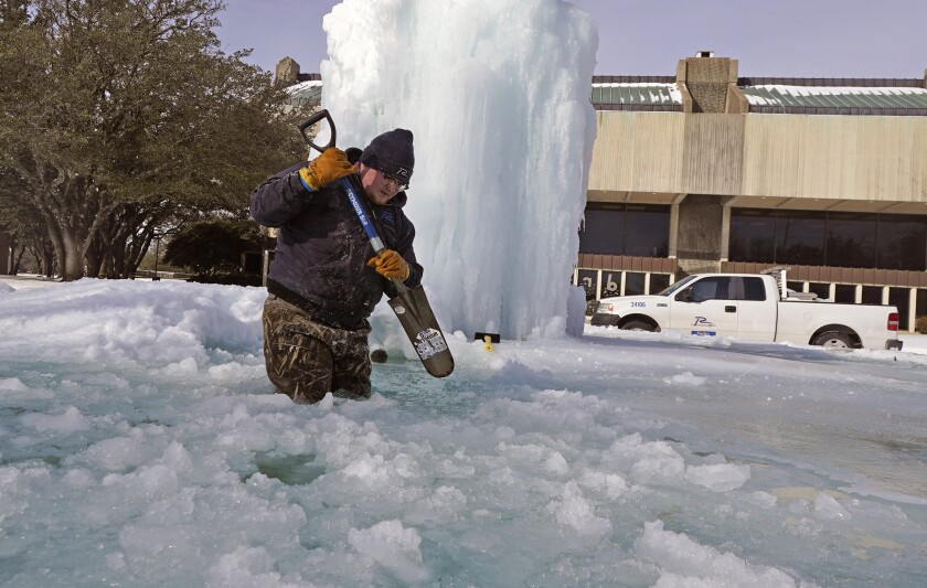 A city worker breaks the ice of a frozen fountain on Tuesday in Richardson, Texas.