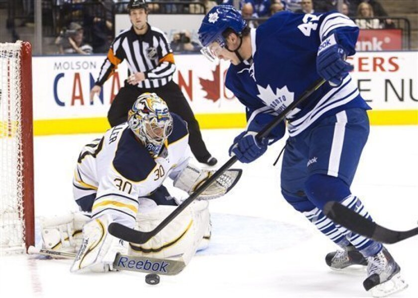 Toronto Maple Leafs forward Tyler Bozak, right, is blocked by Buffalo Sabres goalie Ryan Miller, left, during the second period of an NHL hockey game in Toronto on Saturday, March 31, 2012. (AP Photo/The Canadian Press, Nathan Denette)