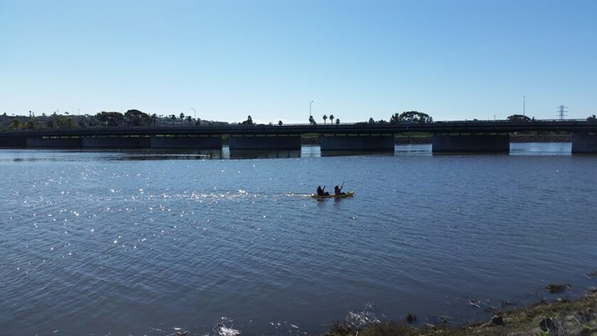 Kayakers collect trash in the estuary area of the San Diego River as part of an annual cleanup event.