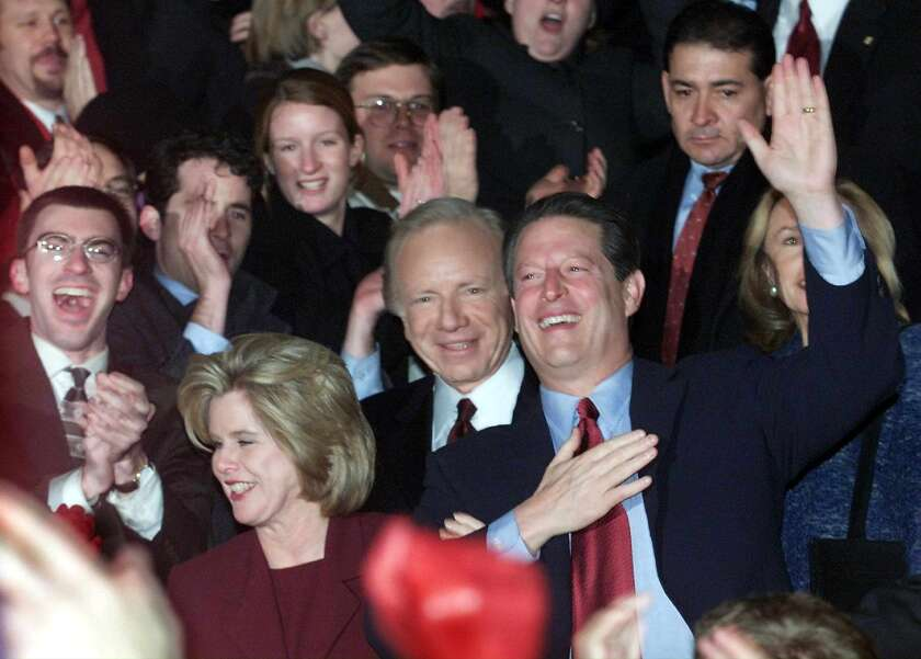 Vice President Al Gore, center, his running mate Joe Lieberman to his right and Gore's wife, Tipper, lower left, greet supporters following Gore's concession speech on Dec. 13, 2000.
