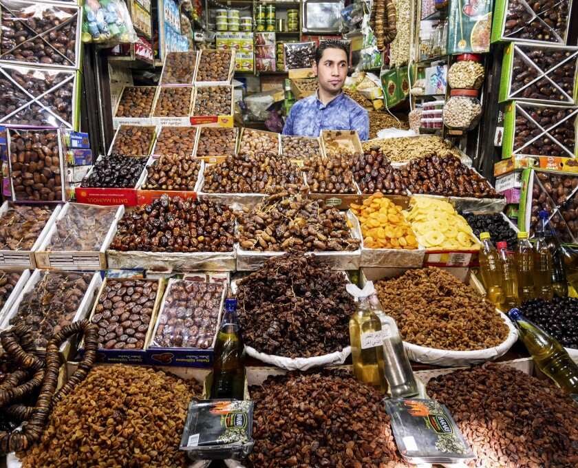 FEZ, MOROCCO - A man hawks dates and other dried fruits in one of the thousands of stalls in the sou