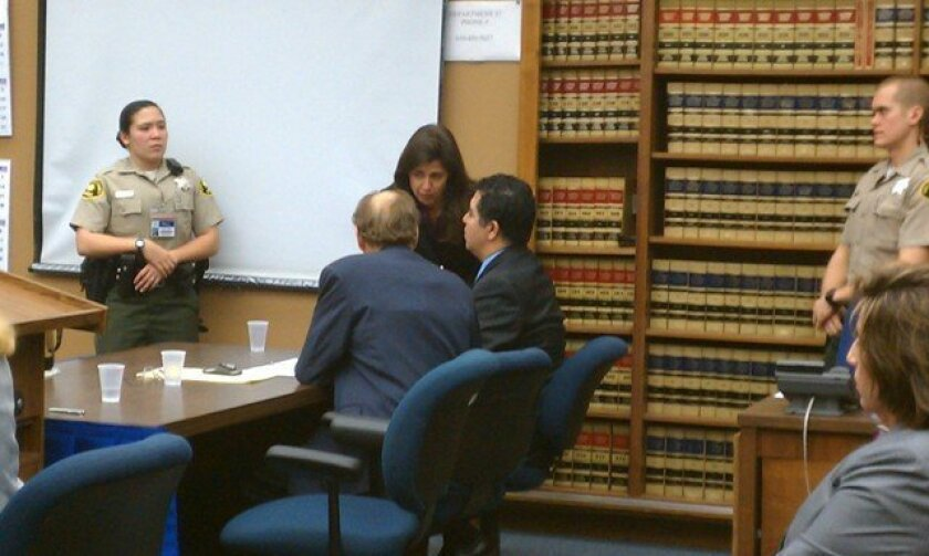 Anthony Arevalos (center) confers with his attorneys while verdicts are being read.