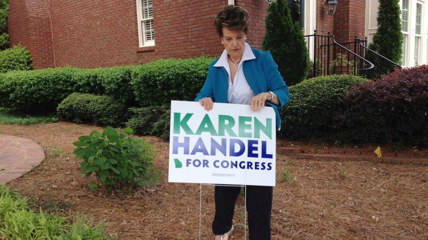 Bev Wingate places a Karen Handel campaign sign outside her home in Dunwoody, Ga.,on April 19, 2017.
